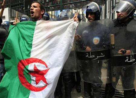 Riot policemen stand guard in front of a university entrance while a university student with an Algerian flag chants slogans during a demonstration in which they demand political change in Algiers May 2, 2011. REUTERS/Zohra Bensemra