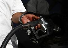 Водитель заправляет машину на АЗС JJ's Express Gas Plus в Финиксе, штат Аризона, 10 августа 2011 года. Потребительские цены в США выросли сильнее ожиданий в июле из-за скачка цен на бензин, но замедление базовой инфляции подтвердило мнение Федрезерва о слабой инфляционной ситуации. REUTERS/Joshua Lott