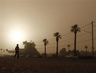 A pedestrian walks along Indian School Road during a dust storm in Phoenix, Arizona August 18, 2011. REUTERS/Joshua Lott