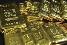 Золотые слитки в офисе CPoR в Париже 25 ноября 2010 года. Цены на золото продолжают бить рекорды в пятницу, так как инвесторы уходят в безопасные активы, убегая от потерь на фондовых рынках, активно снижающихся второй день подряд из-за опасений о замедлении роста мировой экономики и неутешительных перспектив европейских банков.  REUTERS/Jacky Naegelen