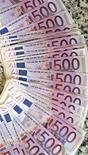 """Купюры валюты евро в банке в Мадриде 13 января 2011 года. Единая европейская валюта отыграла потери в ходе пятничных торгов за счет приказов """"стоп-лосс"""", но по- прежнему находится под давлением на фоне ухудшающегося прогноза роста мировой экономики и опасениях о том, что банки еврозоны, возможно, испытывают трудности с кредитованием. REUTERS/Andrea Comas"""