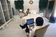 <p>A man sits with his computer at a furniture and chinaware booth during the Summer Fair in Moscow July 4, 2010. The fair,a spin-off of the Millionaire Fair, showcases luxury goods and services. REUTERS/Sergei Karpukhin</p>