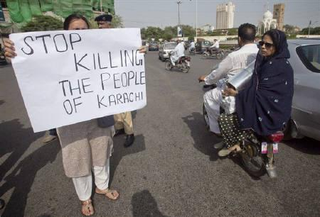 A family rides past on a motor bike as an activist of the civil society group Karachi Concerned Citizen Forum (KCCF) holds a placard along a road in Karachi August 20, 2011.  REUTERS/Akhtar Soomro