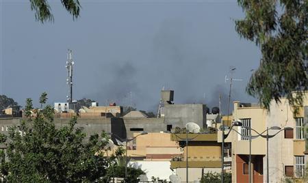 Smoke rises from the skyline in Tripoli August 21, 2011. REUTERS/Paul Hackett