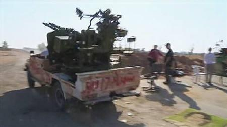 Libyan rebel trucks with anti-aircraft guns along with other trucks drive to Azizia on the road between Bir Ghanem and Azizia, in this still image taken from video on August 21, 2011. REUTERS/via Reuters TV