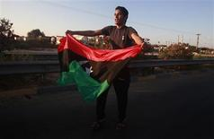 <p>A man waves the Libyan rebel flag during a celebration in the town of Maia after fighters pushed pro-Gaddafi government forces back to within 25 kms (15 miles) of Tripoli, August 21, 2011. REUTERS/Bob Strong</p>