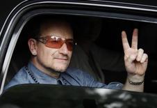 Лидер U2 Боно приветствует поклонников на выезде из гостиницы в Мехико, 11 мая 2011 года. Боно опроверг в воскресенье информацию о том, что он был направлен в больницу после жалоб на боли в груди во время отдыха на юге Франции. REUTERS/Henry Romero