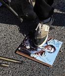 Ливийские повстанцы топчут изображение Муаммара Каддафи в Триполи, 22 августа 2011 года. Мировое сообщество отреагировало на последние успехи ливийских мятежников новыми призывами к Муаммару Каддафи, предложив ему незамедлительно уйти в отставку и не продлевать агонию его режима, дабы избежать лишнего кровопролития. REUTERS/Bob Strong