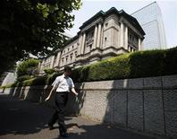 Мужчина проходит мимо здания Банка Японии в Токио 11 августа 2011 года. Банк Японии обдумает дальнейшее смягчение монетарной политики, возможно на экстренном заседании, если укрепление иены удешевит японские акции достаточно для того, чтобы испортить деловые настроения, сообщили источники.  REUTERS/Yuriko Nakao