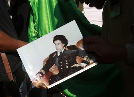 Libyan rebel fighters burn a picture of Muammar Gaddafi at a checkpoint in Tripoli's Qarqarsh district August 22, 2011. REUTERS/Bob Strong
