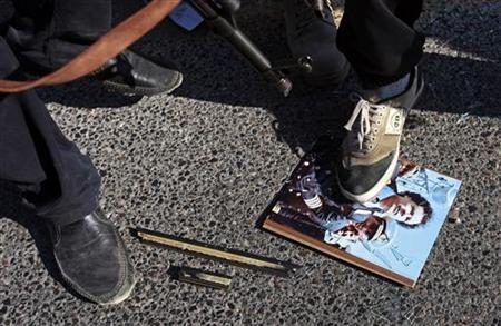 Libyan rebel fighters step on a picture of Muammar Gaddafi at a checkpoint in Tripoli's Qarqarsh district August 22, 2011. REUTERS/Bob Strong