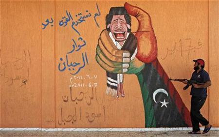 A Libyan rebel fighter walks past graffiti depicting Col Muammar Gaddafi at a checkpoint near Yafran in western Libya August 5, 2011. REUTERS/Bob Strong