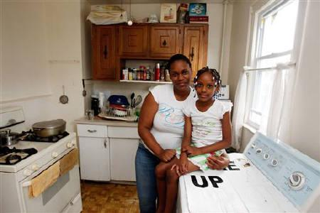 Tashawna Green,  21, poses for a portrait with her daughter, Taishaun, 6, at her home in Queens Village, New York August 21, 2011. REUTERS/Jessica Rinaldi