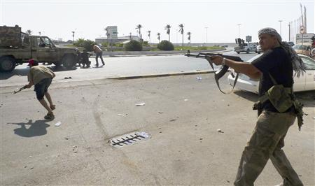 Libyan rebel fighters return fire during an attack by pro-Gaddafi forces after rebels seized a Gaddafi army women's officer training center in Tripoli August 22, 2011. REUTERS/Bob Strong