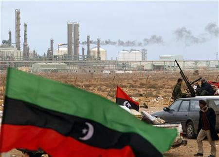 The Kingdom of Libya flag in front of a refinery in Ras Lanuf, March 8, 2011. REUTERS/Goran Tomasevic