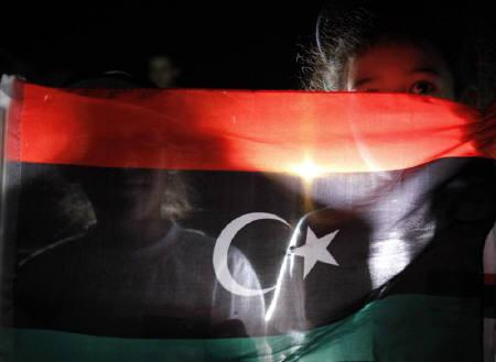 Young Libyans living in Jordan look out from behind a Kingdom of Libya flag during a protest against Libya's leader Muammar Gaddafi outside the Libyan embassy in Amman August 22, 2011. REUTERS/Ali Jarekji