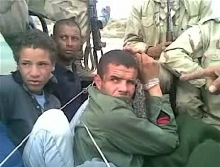 EDITOR'S NOTE: REUTERS CANNOT INDEPENDENTLY VERIFY CONTENT VIDEO FROM WHICH THIS STILL IMAGE WAS TAKEN. A still image from mobile phone video footage obtained by the Misrata-based Human Rights Activists Association between February and July 2011, and purportedly taken from the mobile phone of a captured government soldier, shows what appears to be Gaddafi loyalists beating two men in civilian clothes in Misrata. The men being assaulted, part of a group tied up in the back of a truck, are ordered to chant pro-Gaddaffi slogans by another group of men, some of whom are wearing uniform. REUTERS/Human Rights Activists Association via Reuters TV