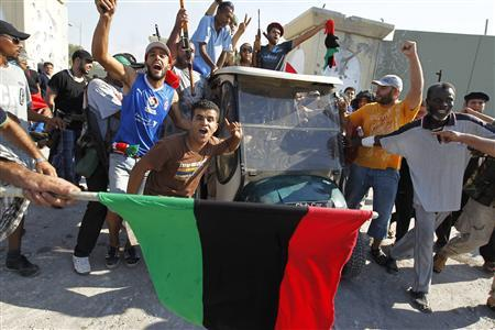 Libyan rebel fighters celebrate near a golf buggy belonging to Muammar Gaddafi at the entrance of Bab al Aziziya compound in Tripoli, August 23, 2011. REUTERS/Zohra Bensemra
