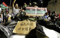 Ливийские повстанцы на Зеленой площади в Триполи, переименованной в Площадь мучеников, 23 августа 2011 года. Ливийские повстанцы захватили вечером во вторник столичную резиденцию Муаммара Каддафи, нанеся, возможно, решающий удар по режиму правящего североафриканской страной более 40 лет лидера. REUTERS/Zohra Bensemra