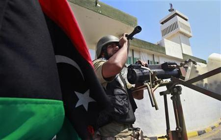 A Libyan rebel fighter keeps watch after rebels seized control of the Gaddafi army women's officer training center in Tripoli's Qarqarsh district August 22, 2011. REUTERS/Bob Strong