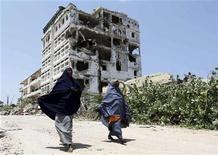 <p>Somali women walk past a destroyed building, a result of a four-year insurgency which has killed tens of thousands of people, in Kaaran district, south of the capital Mogadishu August 23, 2011. REUTERS/Feisal Omar</p>