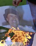 Работник посольства Ливии в Буэнос-Айресе сжигает портрет Муаммара Каддафи, 23 августа 2011 года. Отвоевавшие большую часть Ливии повстанцы продолжают биться за пять процентов территории страны и предложили больше $1 миллиона за правящего страной более 40 лет полковника Муаммара Каддафи - живого или мертвого. REUTERS/Marcos Brindicci