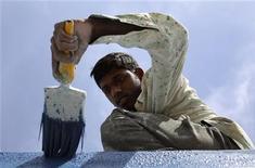 Рабочий красит стену нового жилого комплекса в Ахмедабаде, 17 февраля 2011 года. Двое британских заключенных покрасили дом бывшего министра, выполняя общественные работы. REUTERS/Amit Dave