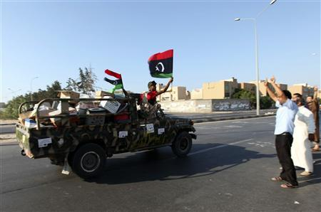 Rebel fighters are greeted on streets of Janzour, west of Tripoli, August 23, 2011. REUTERS/Ismail Zitouny