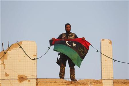 A Libyan rebel holds a Kingdom of Libya flag at Bab Al-Aziziya compound in Tripoli August 23, 2011. REUTERS/Louafi Larbi