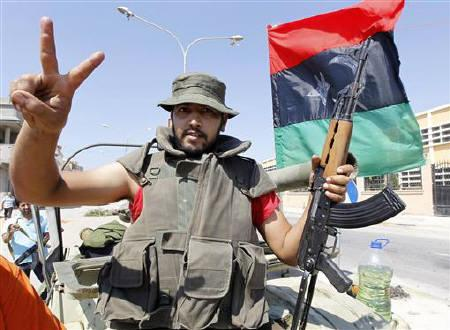 A rebel makes the victory sign near Bab Al-Aziziya in Tripoli August 24, 2011. REUTERS/Louafi Larbi