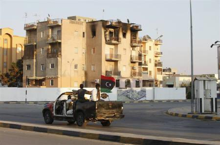 Libyan rebels on a military vehicle ride past a damaged apartment building along a street in Tripoli August 24, 2011. RUTERS/Ismail Zitouny