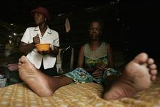 Aids patient Sannah Seetotale (R) waits to receive her food from volunteer worker Matshidiso Masuku in Orange Farm in Johannesburg November 29, 2006.     REUTERS/Siphiwe Sibeko