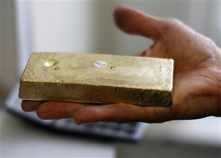 Gold dealer Stan Morton holds a block of gold valued at $63,000 in Los Angeles, California August 23, 2011. Gold prices retreated in choppy trade on Tuesday after earlier hitting record highs as a recovery in appetite for assets seen as higher risk, such as stocks, took the steam out of a rally that many saw as overdone above $1,900 an ounce. REUTERS/Lucy Nicholson