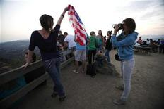 <p>A woman holds a U.S. flag while posing for a photo as she waits for Independence Day fireworks in Griffith Park in Los Angeles, July 4, 2011. REUTERS/Mario Anzuoni</p>