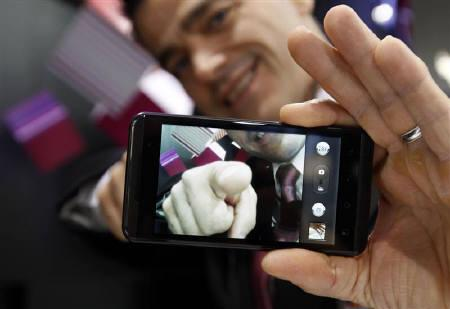 A man displayed the LG Optimus 3D during the GSMA Mobile World Congress in Barcelona February 17, 2011. REUTERS/Gustau Nacarino/Files
