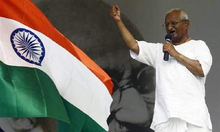 Social activist Anna Hazare gestures while addressing his supporters on the tenth day of his fasting as a national flag flutters at the Ramlila grounds in New Delhi August 25, 2011. REUTERS/Adnan Abidi/Files