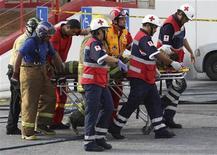 Пожарные везут на носилках своего коллегу после нападения на казино в Монтеррее 25 августа 2011 года. Вооруженные люди сожгли по меньшей мере 53 человека в казино на севере Мексики, сообщили власти. REUTERS/Victor Hugo Valdivia