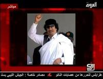 """Снимок ливийского лидера Муаммара Каддафи, прикрепленный сирийским телеканалом Al-Orouba во время трансляции его аудиообращения 25 августа 2011 года. Ливийский лидер Муаммар Каддафи в четверг призвал сторонников маршировать в Триполи и """"очистить"""" столицу от повстанцев, которых назвал """"крысами, крестоносцами и безбожниками"""". REUTERS/Al-Orouba via Reuters TV"""