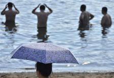 Люди стоят в воде на пляже во Владивостоке  21 августа 2011 года. Власти Хасанского района Приморья в пятницу сняли запрет на купание в Японском море, введенный после атаки акулы на пловцов, хотя попытки изловить хищницу успехом не увенчались. REUTERS/Yuri Maltsev