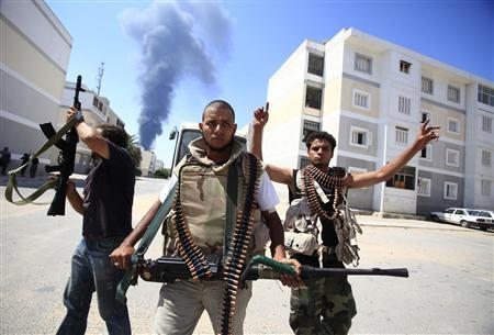 Libyan rebel fighters react as they search for snipers while fighting for the final push to flush out Muammar Gaddafi's forces in Abu Slim area in Tripoli, August 25, 2011.REUTERS/Zohra Bensemra
