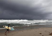 """Серфер идет по пляжу под дождем во Флориде 25 августа 2011 года. Северная Каролина готовится к приближению урагана """"Айрин"""": города на побережье находятся в режиме повышенной готовности и миллионы отдыхающих прервали свое пребывание на пляжах. REUTERS/Joe Skipper"""