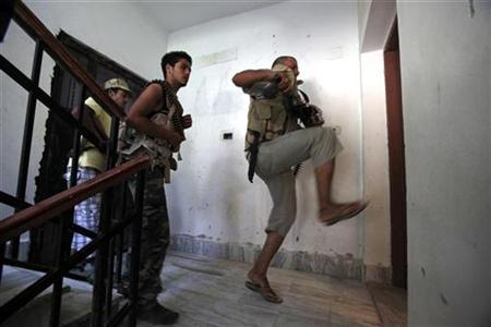 A Libyan rebel fighter kicks down a door during a house search for snipers in the final push to flush out Muammar Gaddafi's forces in Abu Slim area in Tripoli, August 25, 2011. REUTERS/Zohra Bensemra
