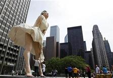 <p>A man jokingly looks under the dress of a 26-foot tall statue of Marilyn Monroe in Chicago, July 15, 2011. REUTERS/Jim Young</p>