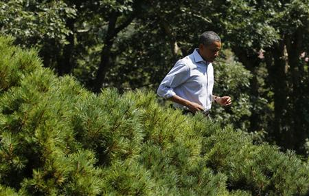 President Barack Obama walks briskly to the lectern to deliver a statement on Hurricane Irene from his vacation on Martha's Vineyard in Massachusetts August 26, 2011. REUTERS/Kevin Lamarque