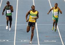 O jamaicano Usain Bolt (centra) cruza a linha de chegada dos 100 metros rasos no campeonato mundial de atletismo. 27/08/2011 REUTERS/David Gray