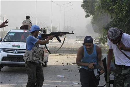 Libyan rebel fighters fire their weapons during a fight for the final push to flush out Muammar Gaddafi's forces in Abu Salim district in Tripoli August 25, 2011. REUTERS/Anis Mili