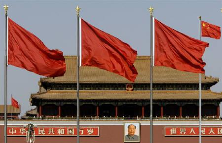 The portrait of Chairman Mao Zedong hangs behind red flags, raised during the sitting of parliament, and the Chinese national flag (R) in Beijing's Tiananmen Square March 3, 2008. REUTERS/David Gray/Files