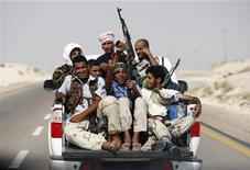 Ливийские повстанцы едут по дороге в 240 километрах в юго-западу от Бенгази, 28 августа 2011 года. Ливийские повстанцы концентрируются вокруг города Сирт, надеясь нанести смертельный удар силам правившего в стране 42 года диктатора Муаммара Каддафи. REUTERS/Darrin Zammit Lupi