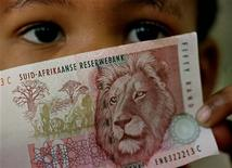A South African child holds a 50 rand note July 2. JN/FMS