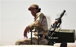 Ливийский повстанец под Бенгази, 29 августа 2011 года. Ливийские повстанцы обвиняют Алжир в содействии насилию: страна стала убежищем для жены Муаммара Каддафи и его троих детей, однако местонахождение бывшего главы Ливии через неделю после его свержения до сих пор остается загадкой. REUTERS/Esam Al-Fetori